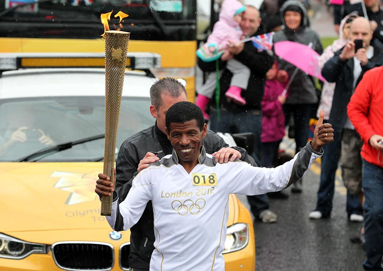 GATESHEAD, UNITED KINGDOM - JUNE 16:  In this handout image provided by LOCOG, Torchbearer Haile Gebrselassie carries the Olympic Flame on the Torch Relay leg between Gateshead and South Shields on June 16, 2012 in Gateshead, England. The Olympic Flame is now on day 29 of a 70-day relay involving 8,000 torchbearers covering 8,000 miles.  (Photo by LOCOG via Getty Images)