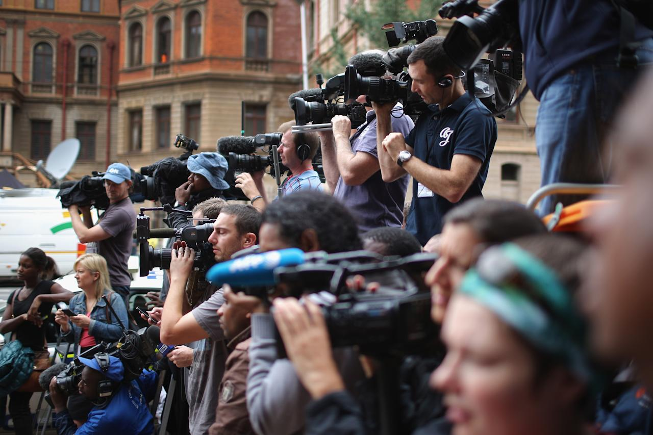 PRETORIA, SOUTH AFRICA - MARCH 06: Television crews wait for the arrival of Oscar Pistorius to North Gauteng High Court for the fourth day of his trial on March 6, 2014 in Pretoria, South Africa. Olympic and Paralympic athlete Oscar Pistorius, aged 27, is accused of murdering his girlfriend Reeva Steenkamp. Pistorius denies the allegation claiming he mistook Steenkamp for an intruder inside their home on Valentines Day 2013. (Photo by Christopher Furlong/Getty Images)