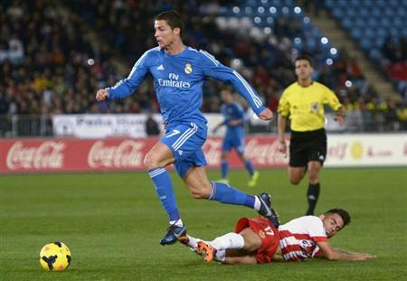 Real Madrid's Ronaldo is challenged by Almeria's Suso during Spanish First Division match in Almeria