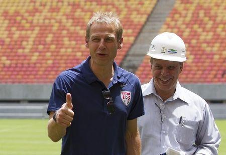 United States national soccer team coach Klinsmann of Germany gestures to photographers while visiting Arena Amazonia stadium with Monteiro in Manaus