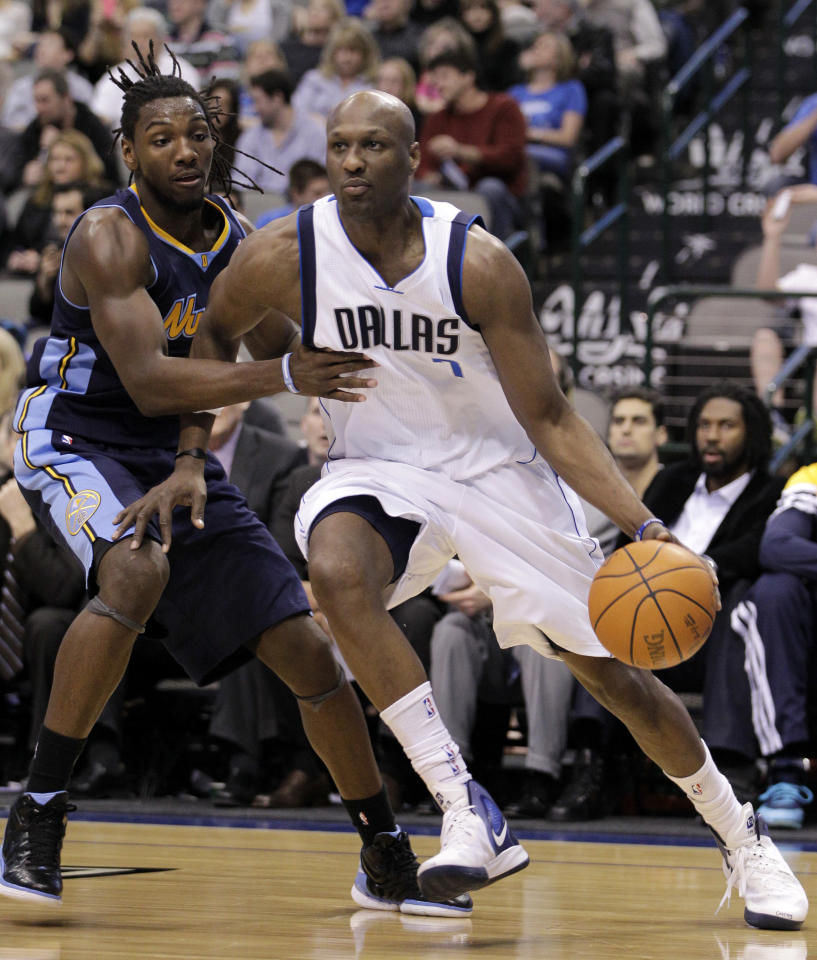 Dallas Mavericks' Lamar Odom, right, drives past Denver Nuggets' Kenneth Faried in the second half of an NBA basketball game Wednesday, Feb. 15, 2012, in Dallas. Odom scored 14 points as Dallas won 102-84. (AP Photo/Tony Gutierrez)