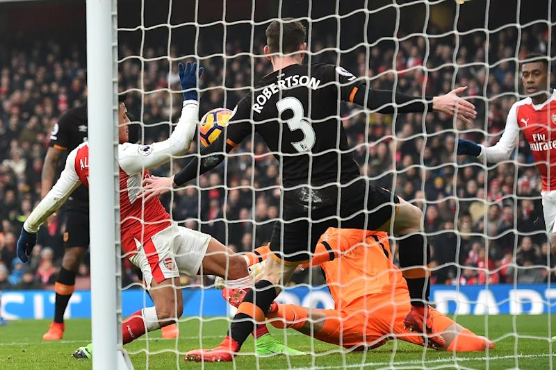 Arsenal striker Alexis Sanchez (L) scores the opening goal of his side's English Premier League match against Hull City at the Emirates Stadium in London on February 11, 2017