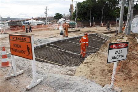 Workers work on areas of infrastructure near the construction site of the Arena das Dunas stadium, in Natal