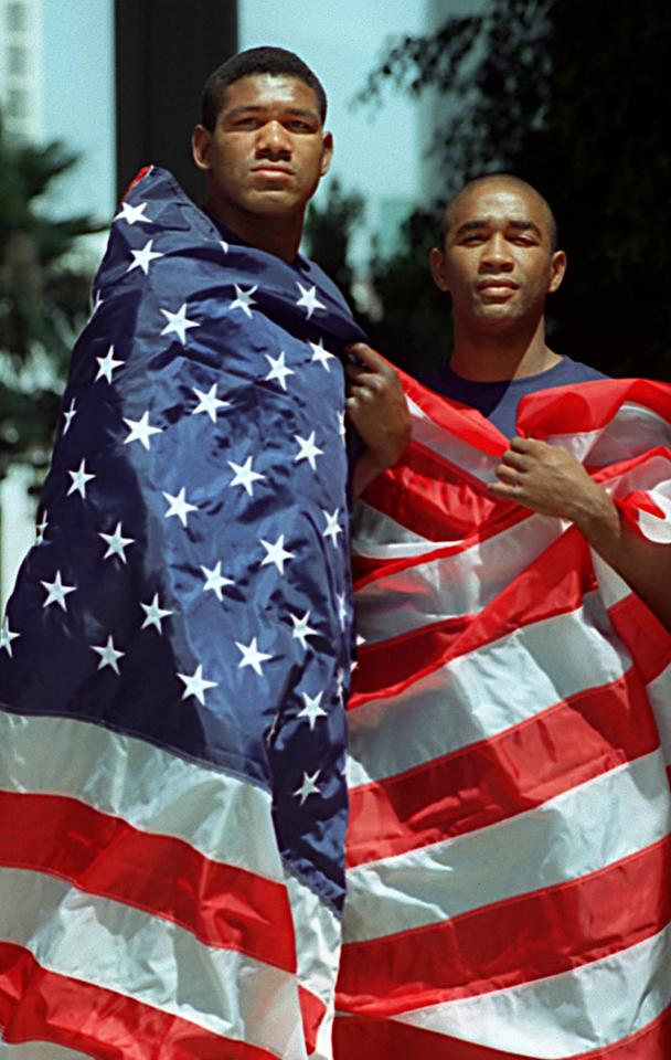 Cuban Olympic Team boxers Ramon Garbey, left, and Joel Casamayor stand draped in a U.S. flag outside the Los Angeles offices of their attorney Frank Ronzio Friday, July 5, 1996. Garbey and Casamayor defected from a boxing training camp in Guadalajara, Mexico last week. They have applied for political asylum. (AP Photo/Susan Sterner)