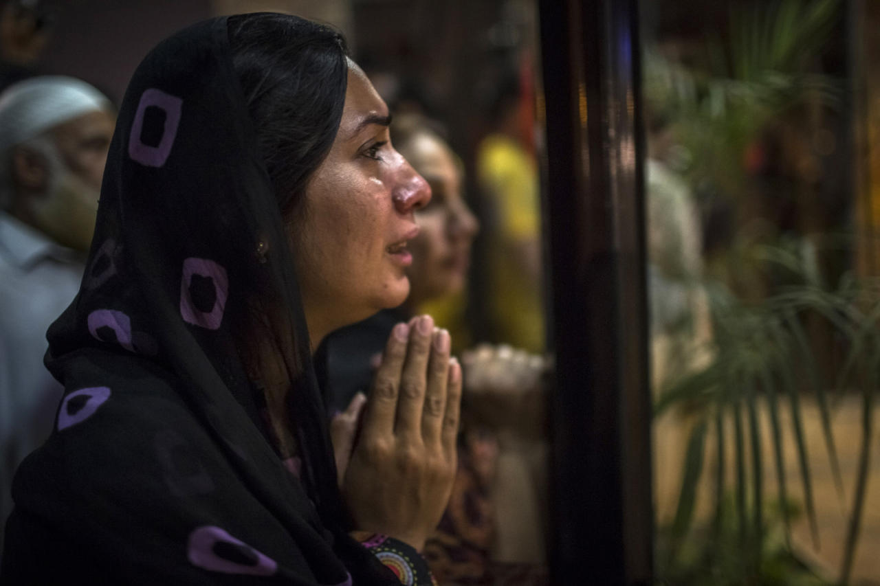 LAHORE, PAKISTAN - MAY 07: A woman believed to be a family member clasps her hands in prayer as people gather at the front doors of the Shaukat Khanum Memorial Cancer Hospital and Research Centre waiting to hear news of the medical condition of Imran Khan, chairman of the Pakistan Tehrik e Insaf (PTI) party, who was injured falling off a lifter during an election campaign rally on May 07, 2013 in Lahore, Pakistan. PTI chairman Imran Khan was injured at a rally in Lahore today after having fallen departing the stage. Pakistan's parliamentary elections are due to be held on May 11. Imran Khan of Pakistan Tehrik e Insaf (PTI) and Nawaz Sharif of the Pakistan Muslim League-N (PMLN) have been campaigning hard in the last weeks before polling. (Photo by Daniel Berehulak/Getty Images)