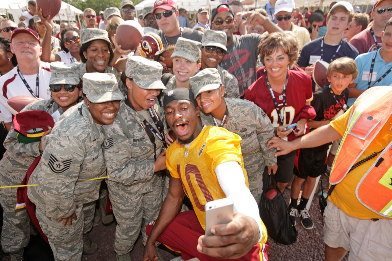 Washington Redskins NFL football team quarterback Robert Griffin III (10) takes a photo with, from left foreground, Lataya Stanley, Jamie Bowser. Angeline Mahoney and Brenda McFarland of the U.S. Air Force, after a joint practice with the New England Patriots in Richmond, Va., Wednesday, Aug. 6, 2014. (AP Photo/Jay Paul)