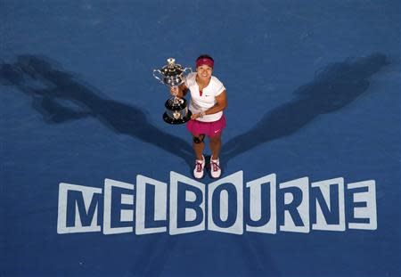 Li Na of China poses with The Daphne Akhurst Memorial Cup after defeating Dominika Cibulkova of Slovakia in their women's singles final match in Melbourne