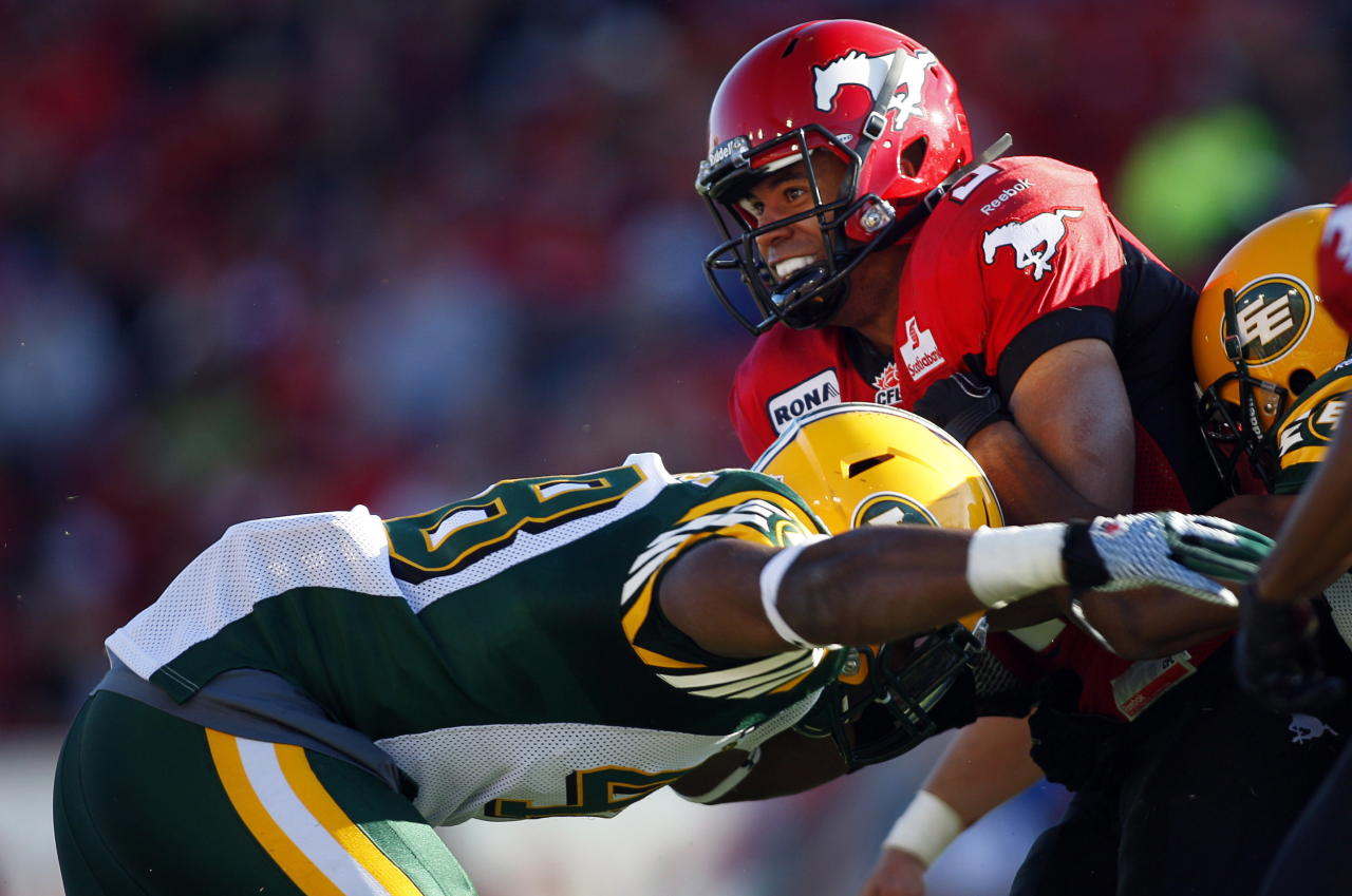 Edmonton Eskimos' Cary Koch, left, tackles Calgary Stampeders' Jon Cornish, during first half CFL pre-season football action in Calgary, Alta., Friday, June 15, 2012. THE CANADIAN PRESS/Jeff McIntosh