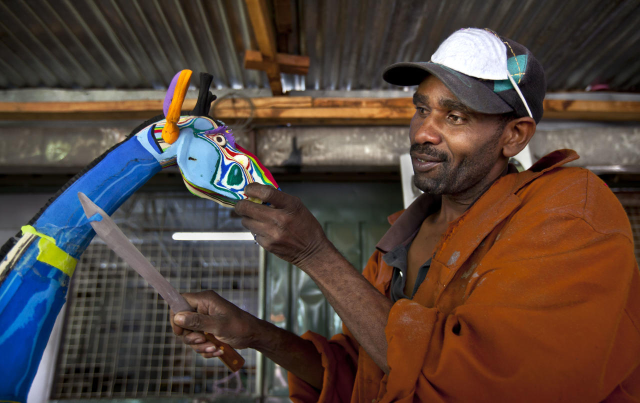 In this photo taken Monday, April 29, 2013, Jackson Mbatha, 40, uses a knife to carve part of the neck of a large giraffe he is making from pieces of discarded flip-flops, at the Ocean Sole flip-flop recycling company in Nairobi, Kenya. The company is cleaning the East African country's beaches of used, washed-up flip-flops and the dirty pieces of rubber that were once cruising the Indian Ocean's currents are now being turned into colorful handmade giraffes, elephants and other toy animals. (AP Photo/Ben Curtis)