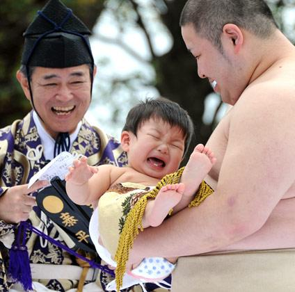 "A student sumo wrestler carrys a crying baby beside a referee (L) clad in a traditional costume during the ""Baby-cry Sumo"" competition at Sensoji temple in Tokyo on April 21, 2012. Some 100 babies aged under one took part in the annual baby crying contest. Japanese parents believe that sumo wrestlers can help make babies cry out a wish to grow up with good health.    AFP PHOTO/Toru YAMANAKA"