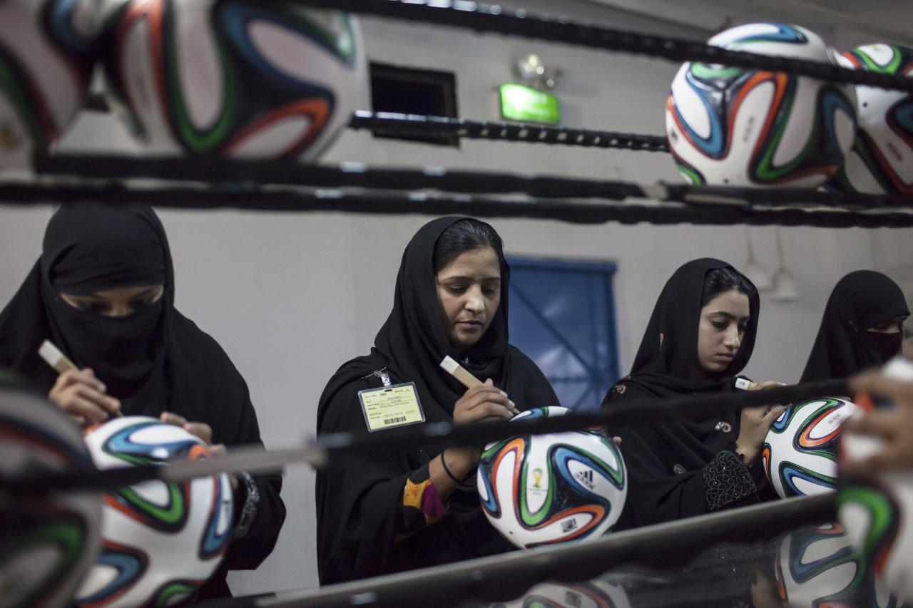 Employees conduct a final check to fix any cavities in the seams of balls inside the soccer ball factory that produces official match balls for the 2014 World Cup in Brazil, in Sialkot, Punjab province May 16, 2014. It was when he felt the roar of the crowd at the 2006 World Cup in Germany that Pakistani factory owner Khawaja Akhtar first dreamt up a goal of his own: to manufacture the ball for the biggest soccer tournament on the planet. Last year he finally got his chance - but only 33 days to make it happen. Picture taken May 16. REUTERS/Sara Farid (PAKISTAN \ - Tags: SPORT SOCCER WORLD CUP BUSINESS EMPLOYMENT)