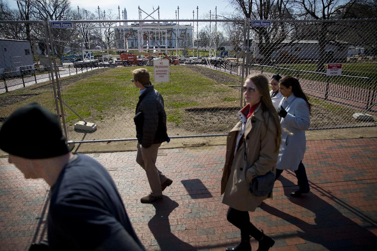 In this photo taken Feb. 17, 2017, pedestrians walk along fencing erected in Lafayette Park, across from the White House in Washington, as work continues with the dismantling of the presidential inauguration reviewing stand. (AP Photo/Pablo Martinez Monsivais)