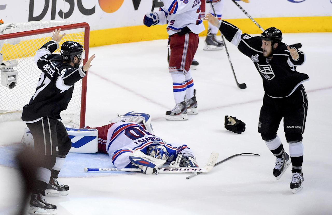 Los Angeles Kings defenseman Alec Martinez, left, celebrates with Kyle Clifford, right, after scoring the winning goal past New York Rangers goalie Henrik Lundqvist, of Sweden, during the second overtime period in Game 5 of an NHL hockey Stanley Cup finals, Friday, June 13, 2014, in Los Angeles.  (AP Photo/Mark J. Terrill)