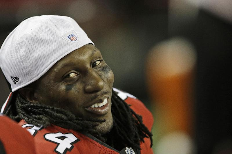 In this Aug. 8, 2013 file photo, Atlanta Falcons wide receiver Roddy White (84) smiles on the sideline during a preseason game against the Cincinnati Bengals in Atlanta. On the eve of training camp, the Falcons have agreed to terms on a new contract with receiver White. The Falcons announced the four-year extension Thursday, July 24, 2014