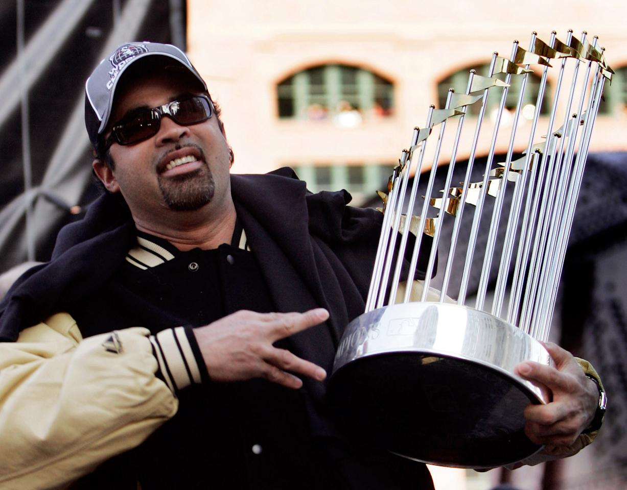Chicago White Sox manager Ozzie Guillen holds the 2005 World Series trophy during his teams victory rally in Chicago, October 28, 2005. The White Sox won the best-of-seven series against the Houston Astros four games to none. REUTERS/John Gress