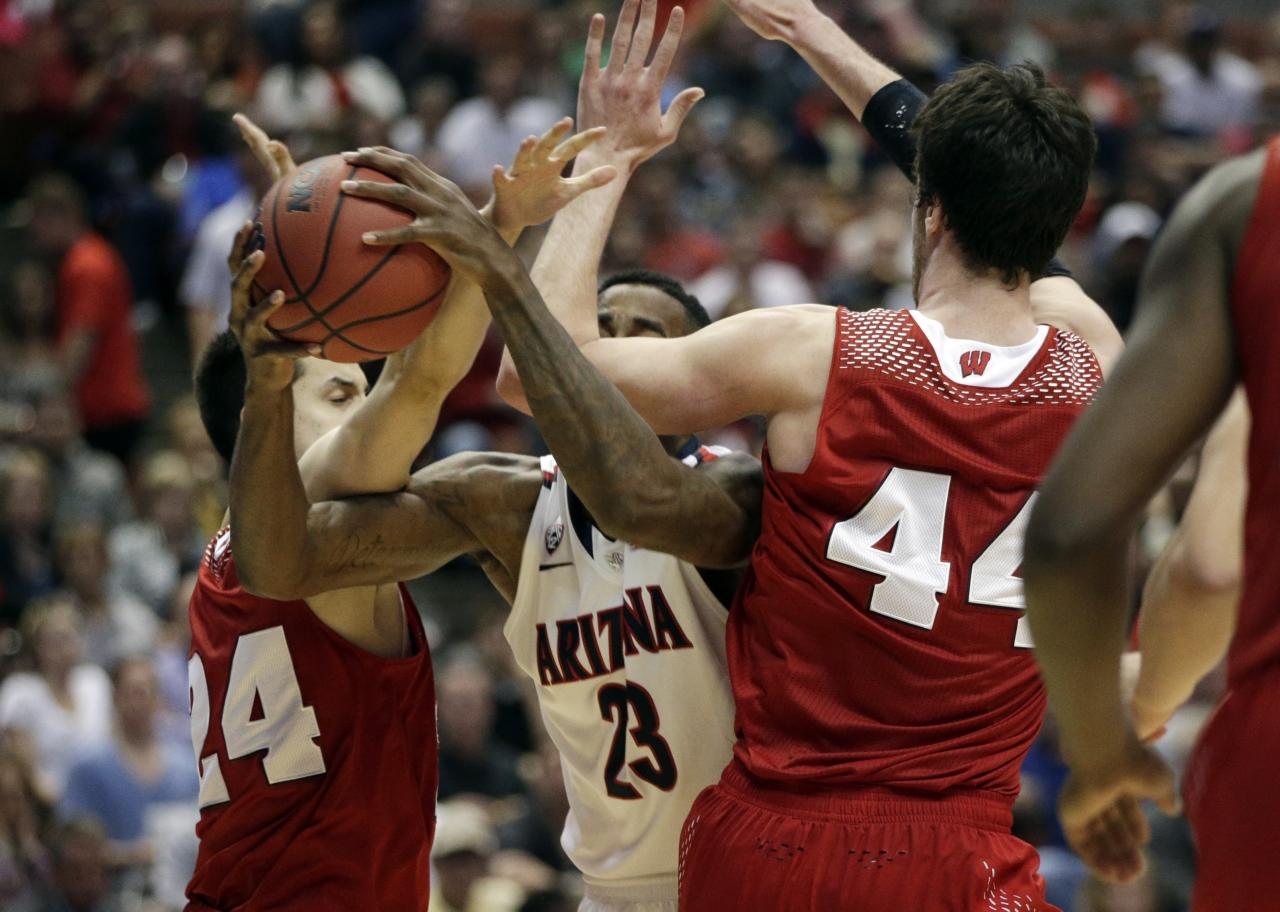 Arizona's Rondae Hollis-Jefferson tries to drive between Wisconsin 's Bronson Koenig (24) and Frank Kaminsky (44) during the second half in a regional final NCAA college basketball tournament game, Saturday, March 29, 2014, in Anaheim, Calif. (AP Photo/Jae C. Hong)
