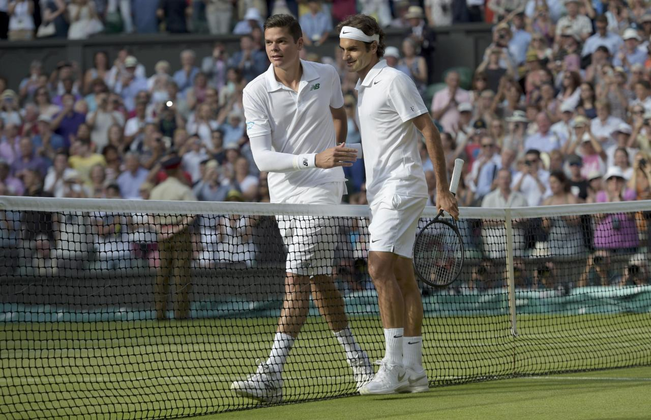 Roger Federer of Switzerland (R) puts an arm around Milos Raonic of Canada after defeating him in their men's singles semi-final tennis match at the Wimbledon Tennis Championships, in London July 4, 2014. REUTERS/Facundo Arrizabalaga/Pool (BRITAIN - Tags: SPORT TENNIS)