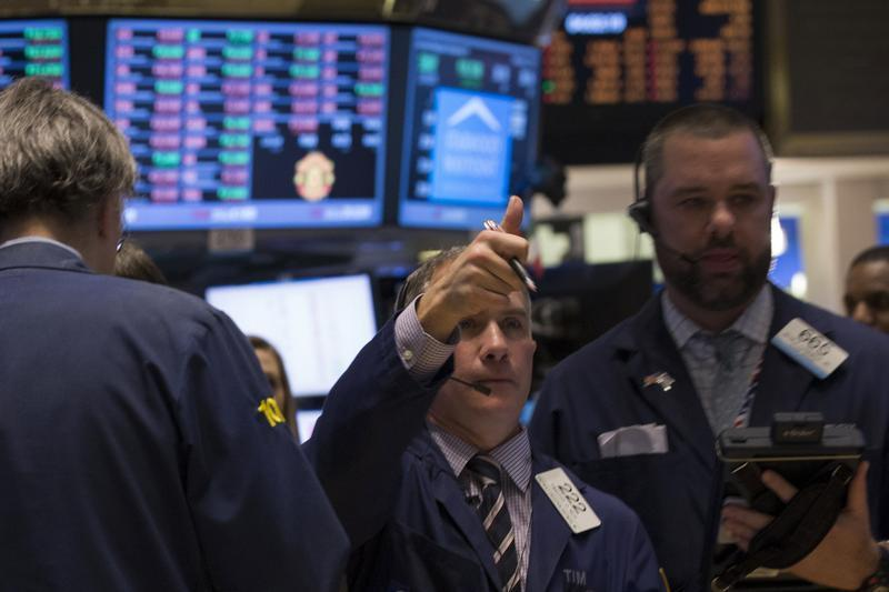 A trader gives a thumbs up while he works on the floor of the New York Stock Exchange