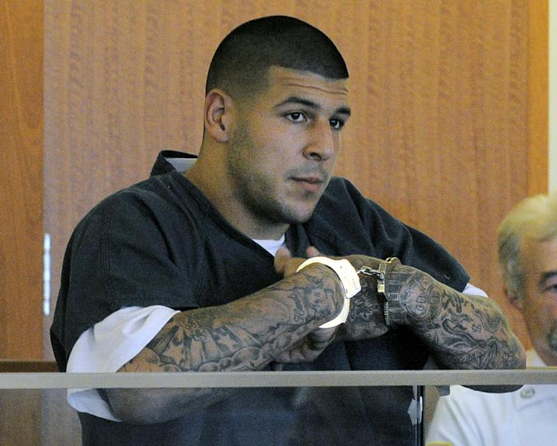 In this June 27, 2013 file photo, former New England Patriots football standout Aaron Hernandez stands during a bail hearing in Superior Court in Fall River, Mass., charged with killing Odin Lloyd. Hernandez is scheduled to be arraigned May 28, 2014, on two unrelated murder charges in the 2012 shooting deaths of Daniel de Abreu and Safiro Furtado in Boston. Prosecutors are also seeking assistance from tattoo artists who may have inked Hernandez's right arm between February 2012 and June 2013. The tattoo artists are considered witnesses, not suspects