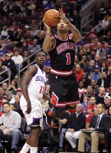 Chicago Bulls' Derrick Rose, right, makes a jump shot as Philadelphia 76ers' Jrue Holiday, left, looks on during the first half of an NBA basketball game, Sunday, March 4, 2012, in Philadelphia. (AP Photo/Tom Mihalek)