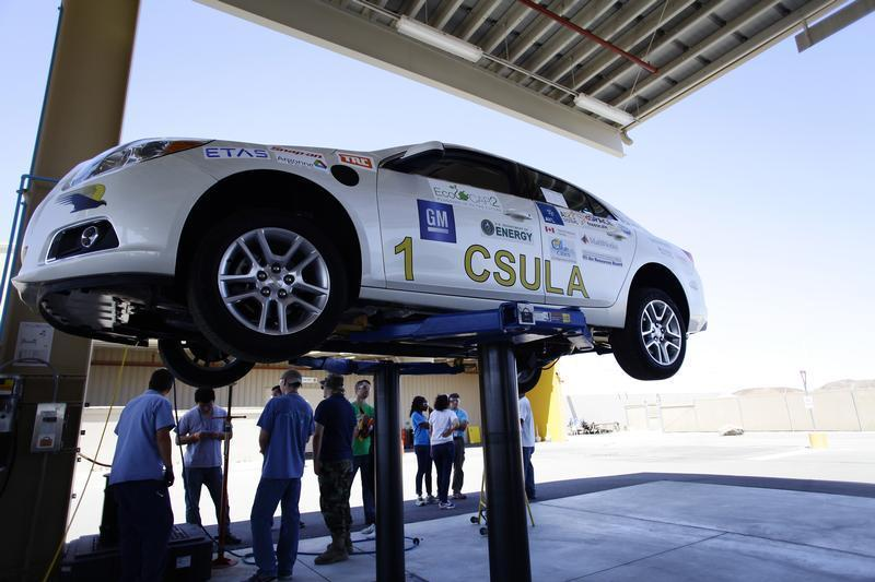 Student engineers from California State University Los Angeles stand by their eco-friendly re-engineered Chevrolet Malibu at the General Motors Desert Proving Ground in Yuma