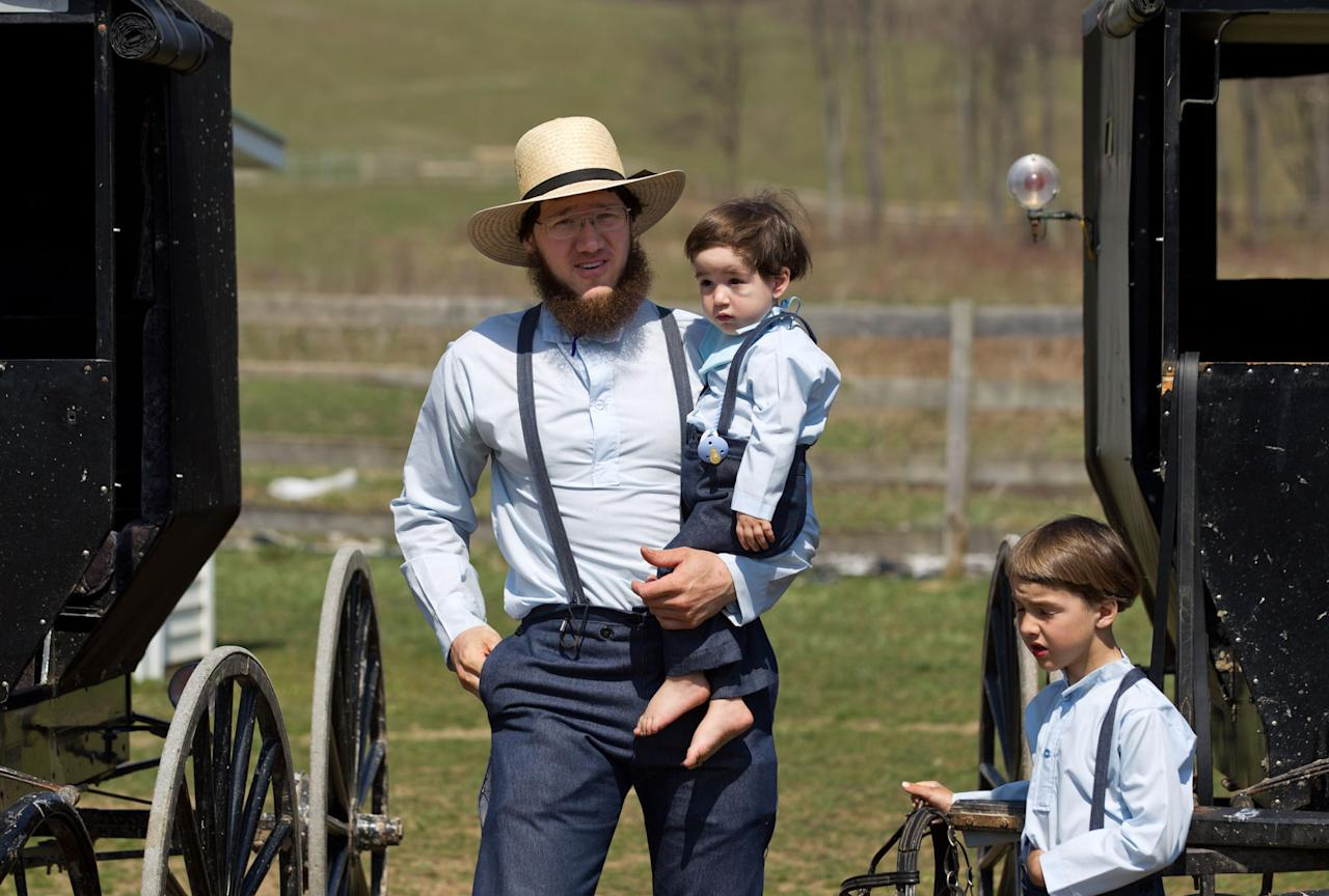 Freeman Burkholder carries his son to the school house for a ceremony to mark the end of the school year Tuesday, April 9, 2013 in Bergholz, Ohio. Burkholder and four women from this tight-knit community in rural eastern Ohio will enter prison on Friday, April 12, joining nine already behind bars on hate crimes convictions for hair- and beard-cutting attacks against fellow Amish. (AP Photo/Scott R. Galvin)