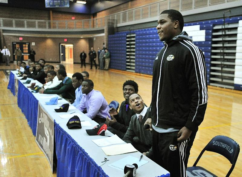 Teammates and schoolmates react after Malik McDowell, right, announces he will be attending Michigan State University to play football during a national signing day ceremony at Southfield High School's gym in Southfield, Mich., Wednesday, Feb. 5, 2014