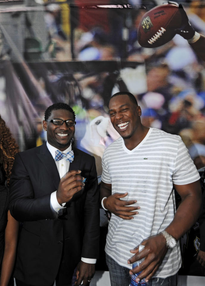 Former San Diego Chargers running back LaDainian Tomlinson, left, jokes around with Chargers tight end Antonio Gates during a news conference at the team's facility, Monday, June 18, 2012, in San Diego. Tomlinson signed a one-day contract with the Chargers and announced his retirement after an 11-year NFL career. (AP Photo/Denis Poroy)