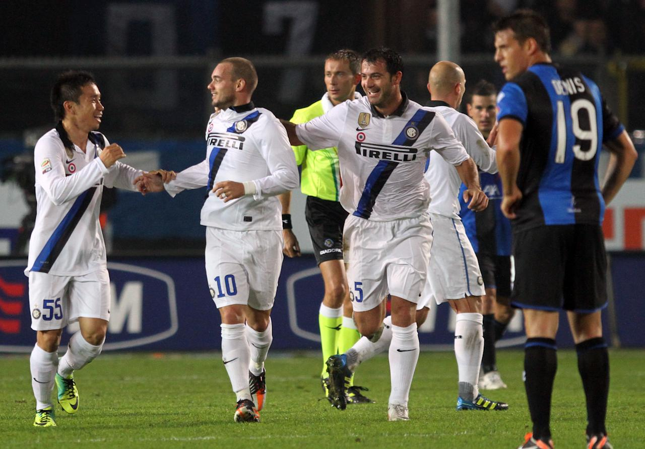Inter's Wesley Sneijder, second left, of the Netherlands, is congratulated by his teammates Yuto Nagatomo, left, of Japan, and Dejan Stankovic, of Serbia, after he scored during a Serie A soccer match against Atalanta in Bergamo, Italy, Wednesday, Oct. 26, 2011. (AP Photo/Felice Calabro')