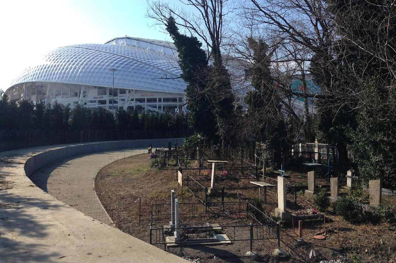 A small cemetery of Old Believers, a purist sect that branched out of the Russian Orthodox in the 17th century, is right in the middle of Olympic Park at the 2014 Winter Olympics in Sochi, Russia, Monday, Feb. 10, 2014. It goes completely unnoticed by passers-by who walk along a round plot of land surrounded by a tinted glass fence and lined with almost identical fir-trees. (AP Photo/Mark Carlson)