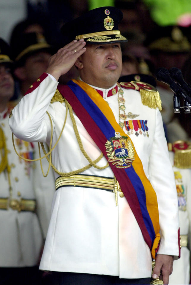 Venezuelan President Hugo Chavez, wearing the full military uniform, salutes while listen the national anthem during the military parade of the 189th anniversary of the Venezuelan Independence, July 5, 2000. (Photo by Andres Leighton/Getty Images)