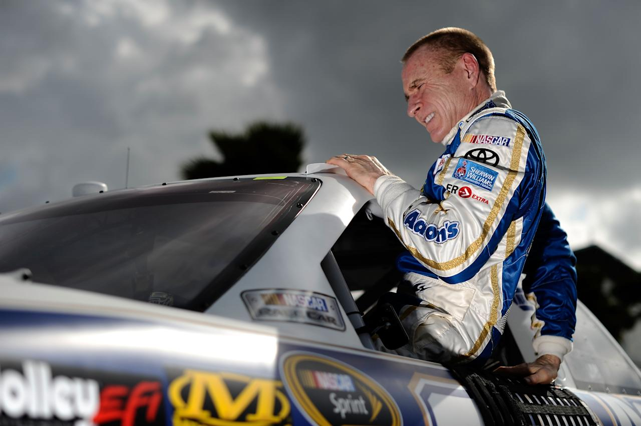 DAYTONA BEACH, FL - FEBRUARY 19:  Mark Martin, driver of the #55 Aaron's Toyota, climbs from his car after qualifying for the NASCAR Sprint Cup Series Daytona 500 at Daytona International Speedway on February 19, 2012 in Daytona Beach, Florida.  (Photo by Jared C. Tilton/Getty Images for NASCAR)