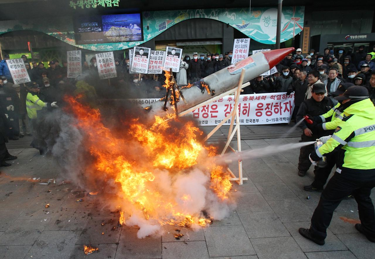 South Korean protesters burn a mock rocket as police officers spray fire extinguishers during a rally denouncing North Korea's rocket launch in Seoul, South Korea, Wednesday, Dec. 12, 2012. North Korea successfully fired a long-range rocket on Wednesday, defying international warnings as the regime of Kim Jong Un took a giant step forward in its quest to develop the technology to deliver a nuclear warhead. (AP Photo/Ahn Young-joon)