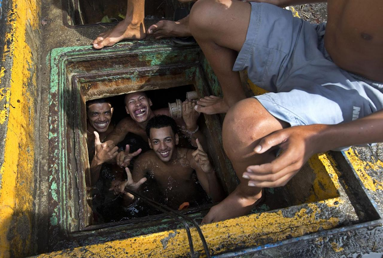 Men pose for a photo from the inside of a cistern of an abandoned building, occupied by squatters, in Rio de Janeiro, Brazil, Wednesday, April 9, 2014. Thousands of people have laid claim to a compound of abandoned office buildings owned by the private telecommunications company Oi, and named their settlement after the state-owned telecommunications Telerj. Authorities are negotiating with squatters to leave peacefully from the area they have occupied for more than a week. (AP Photo/Silvia Izquierdo)