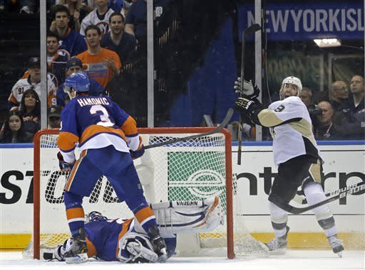 Pittsburgh Penguins right wing Pascal Dupuis, right, reacts after scoring a goal against New York Islanders goalie Evgeni Nabokov, of Kazakhstan, who lies in the crease, as Islanders defenseman Travis Hamonic (3) looks away during the second period of Game 6 of a first-round NHL Stanley Cup playoff hockey series in Uniondale, N.Y., Saturday, May 11, 2013. (AP Photo/Kathy Willens)
