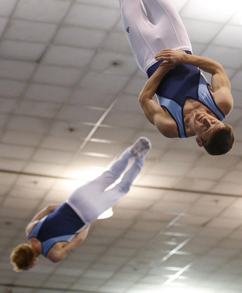 Michael Devine, left, and Jeffery Gluckstein, top right, compete in the synchro trampoline event at the USA Gymnastics Championships in San Jose, Calif., Wednesday, June 27, 2012. The pair placed first. (AP Photo/Jae C. Hong)
