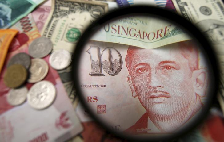 File photo illustration of bank notes and coins of various currencies including the Singapore dollar