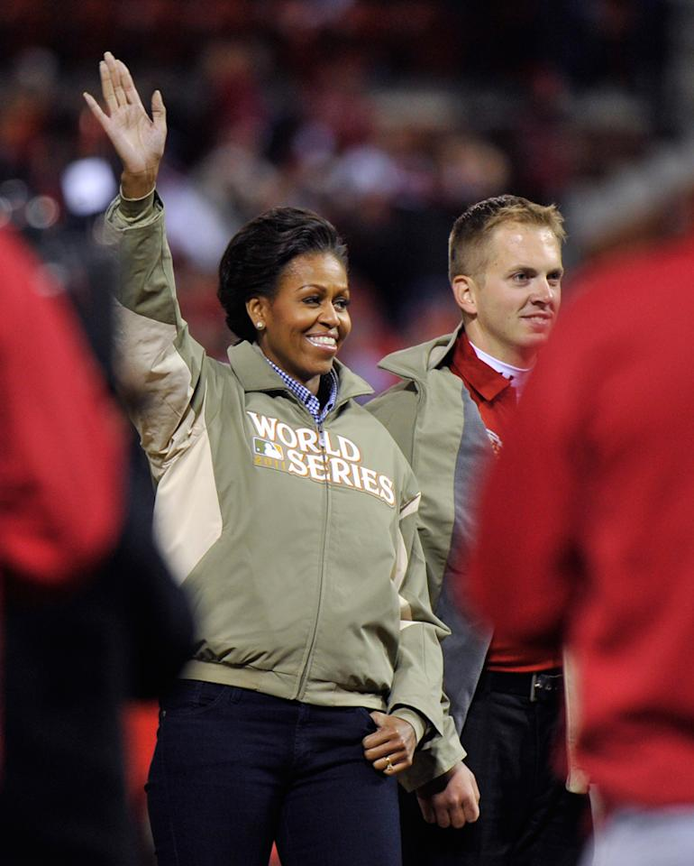 Photo by: (REUTERS/Ray Stubblebine)<br />Michelle Obama at the World Series baseball championship in St. Louis, Missouri, October 19, 2011.-<br />U.S. first lady Michelle Obama waves as she attends the opening pitch of the World Series with Marine and first responder Lance Corporal James Sperry (R) ahead of Game 1 of MLB's World Series baseball championship between the Texas Rangers and the St. Louis Cardinals in St. Louis, Missouri, October 19, 2011.