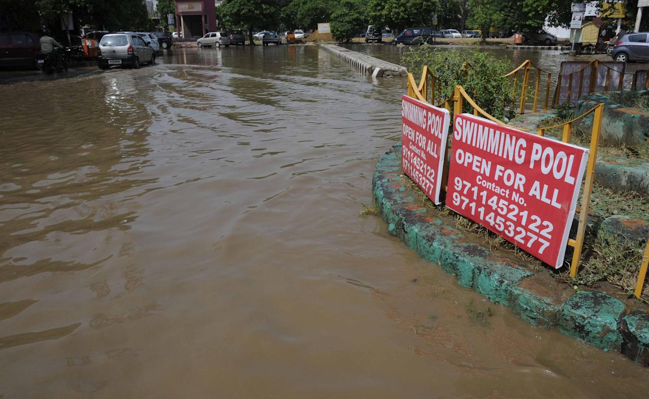 GURGAON, INDIA - JUNE 17: Rain water logging at sector-31 Huda market on June 17, 2013 in Gurgaon, India. The city received 60 mm of rainfall.(Photo by Parveen Kumar/Hindustan Times via Getty Images)
