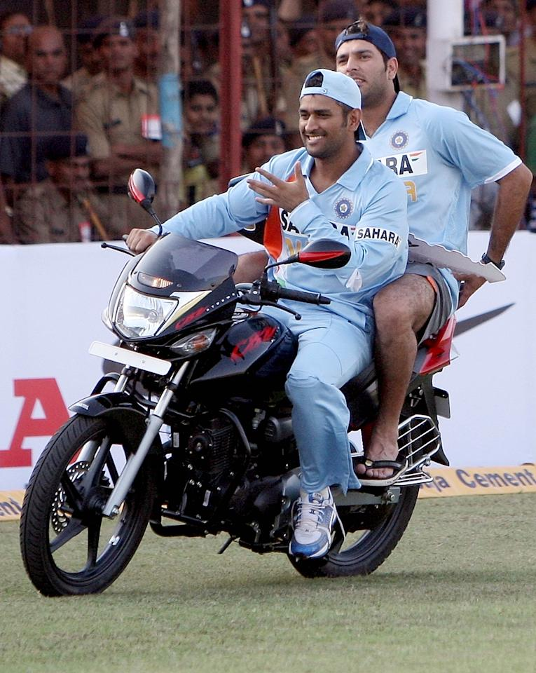 Indian cricketer  and man-of-the-match Yuvraj Singh rides pillion on his prize- a motorbike being driven round the stadium by captain Mahendra Singh Dhoni during the first One Day International (ODI) between India and England at the Madhavrao Scindia cricket ground, in Rajkot on November 14, 2008. India won the match by 158 runs and lead the seven match ODI series 1-0.    AFP PHOTO/Indranil MUKHERJEE