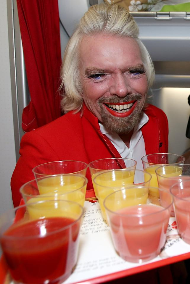 PERTH, AUSTRALIA - MAY 12:  Sir Richard Branson serves drinks prior to his flight to Kuala Lumpur at Perth International Airport on May 12, 2013 in Perth, Australia. Sir Richard Branson lost a friendly bet to AirAsia Group Chief Executive Officer Tony Fernandez after wagering on which of their Formula One racing teams would finish ahead of each other in their debut season of the 2010 Formula One Grand Prix in Abu Dhabi and that the loser would serve as a female flight attendant on board the winner's airline.  (Photo by Paul Kane/Getty Images)