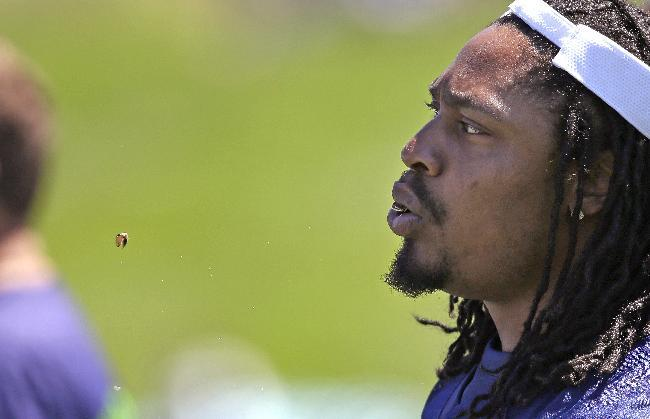 Seattle Seahawks' Marshawn Lynch spits out sunflower seed shells as he looks on during NFL football minicamp Thursday, June 19, 2014, in Renton, Wash