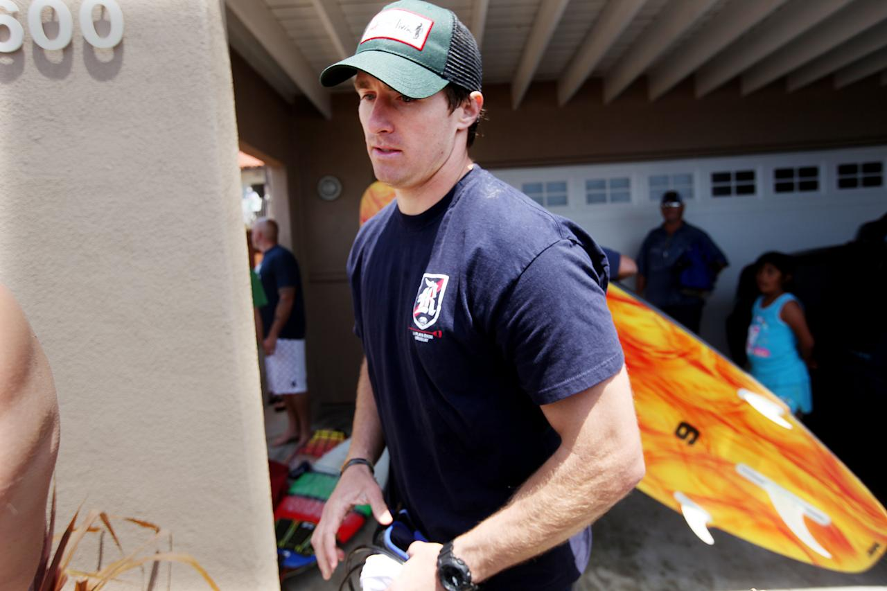"""OCEANSIDE, CA - MAY 6: New Orleans Saints Quarterback Drew Brees walks out after a """"paddle out"""" in honor of NFL star Junior Seau on May 6, 2012 in Oceanside, California.  Seau, who played for various NFL teams including the San Diego Chargers, Miami Dolphins and New England Patriots was found dead in his home on May 2nd of an apparent suicide.  Family members have decided to donate his brain for research on links between concussions and possible depression. (Photo by Sandy Huffaker/Getty Images)"""