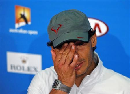 Rafael Nadal of Spain wipes his face at a news conference after losing his men's singles final match against Stanislas Wawrinka of Switzerland at the Australian Open 2014 tennis tournament in Melbourne