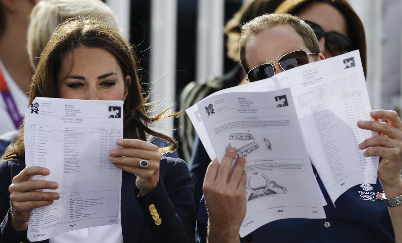 Britain's Catherine, Duchess of Cambridge, and Britain's Prince William, the Duke of Cambridge read a program as they watch the equestrian eventing cross country phase at the 2012 Summer Olympics, Monday, July 30, 2012, in London. (AP Photo/David Goldman)