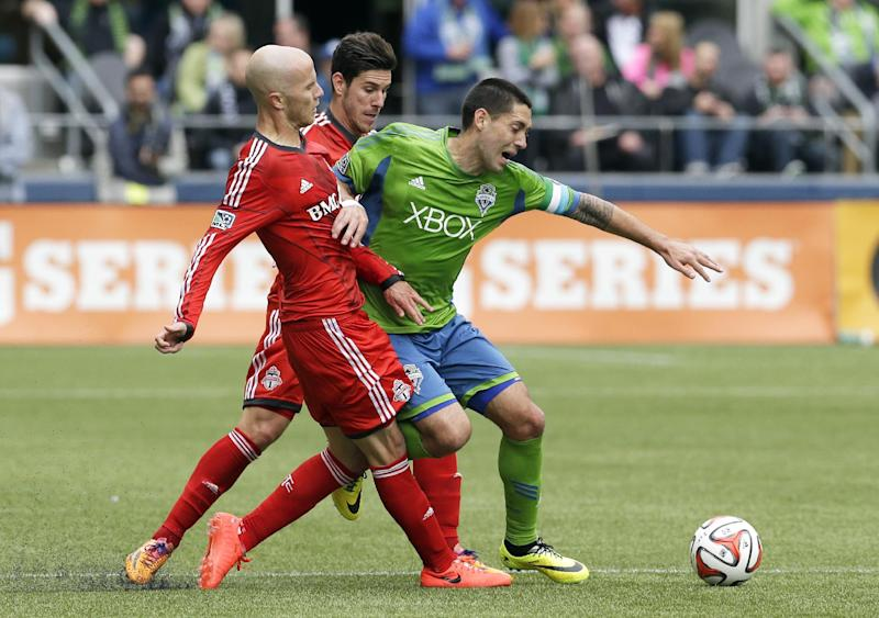 Seattle Sounders' Clint Dempsey, right, battles against Toronto FC's Michael Bradley, left, and Alvaro Rey, center, in the first half of an MLS soccer match on Saturday, March 15, 2014, in Seattle