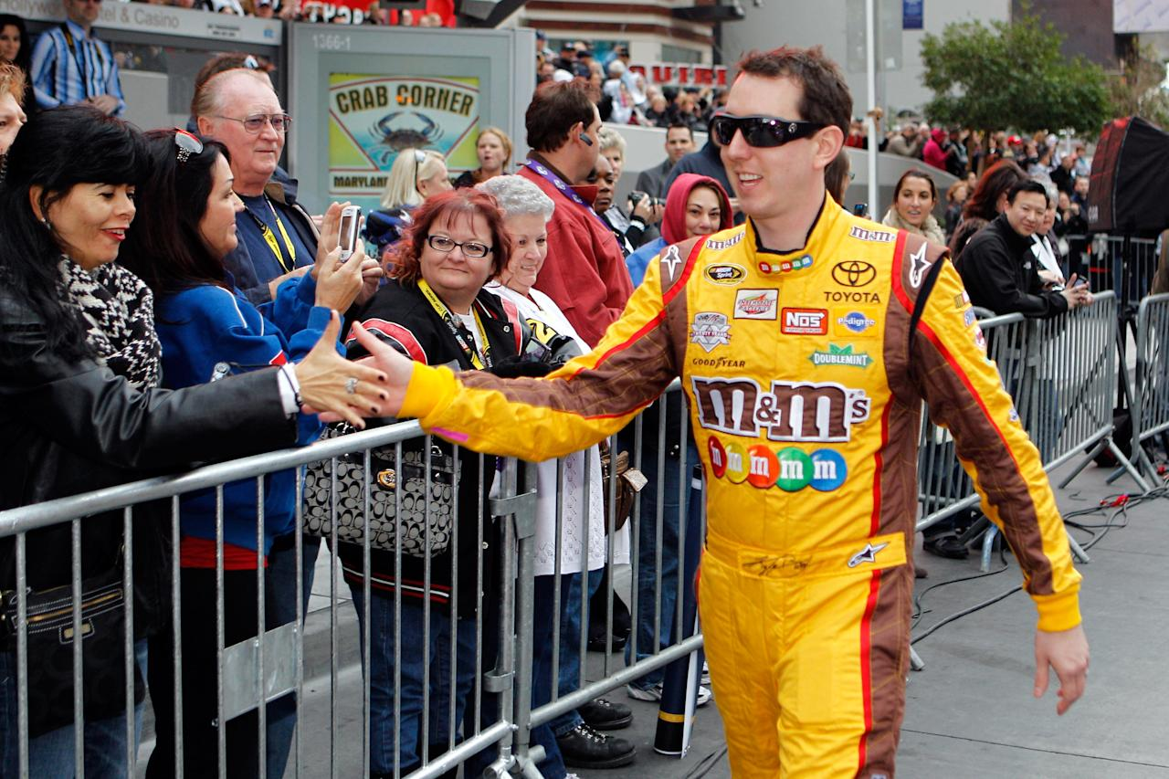 LAS VEGAS, NV - DECEMBER 01:  Kyle Busch, driver of the #18 Interstate Batteries Toyota, greets fans before the NASCAR Victory Lap on the Las Vegas Strip on December 1, 2011 in Las Vegas, Nevada.  (Photo by Chris Graythen/Getty Images for NASCAR)