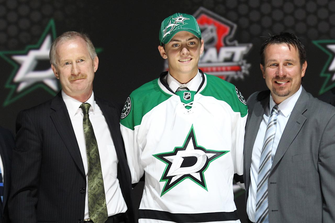 Jun 30, 2013; Newark, NJ, USA; Jason Dickinson poses for a photo with team officials after being introduced as the number twenty-nine overall pick to the Dallas Stars during the 2013 NHL Draft at the Prudential Center. (Ed Mulholland-USA TODAY Sports)