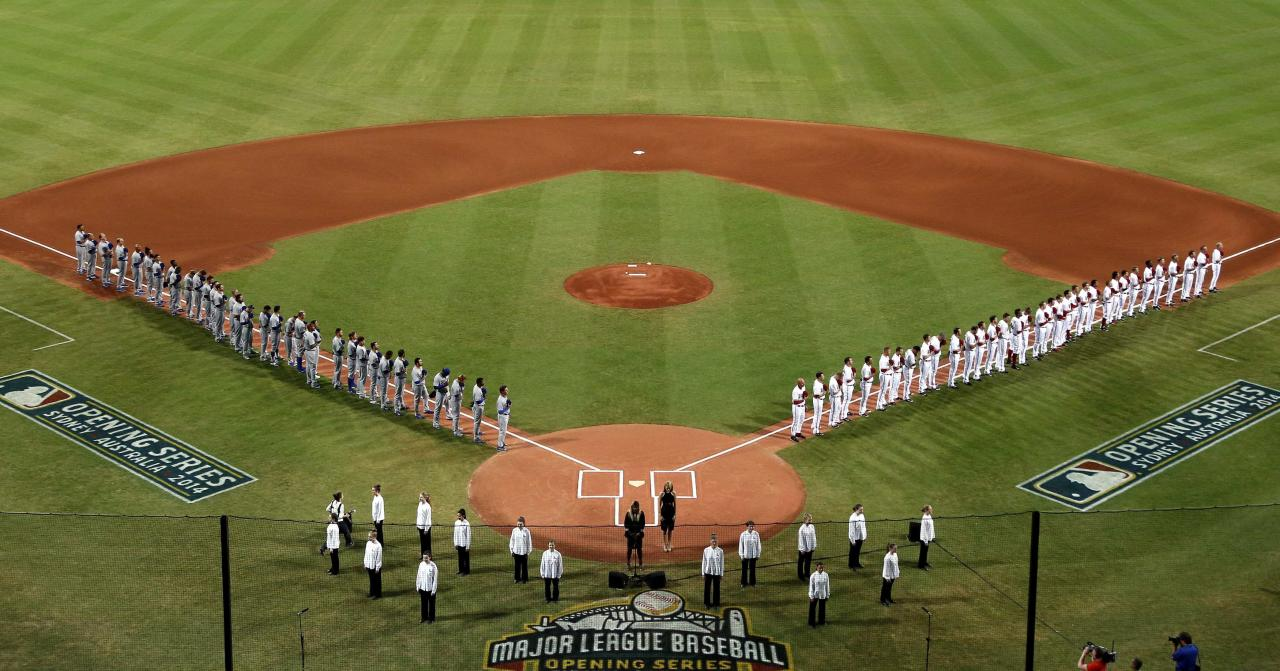 Players from the Arizona Diamondbacks and Los Angeles Dodgers stand together to listen to the national anthems before the start of the opening game of the 2014 Major League Baseball season at the Sydney Cricket Ground March 22, 2014. REUTERS/David Gray (AUSTRALIA - Tags: SPORT BASEBALL)
