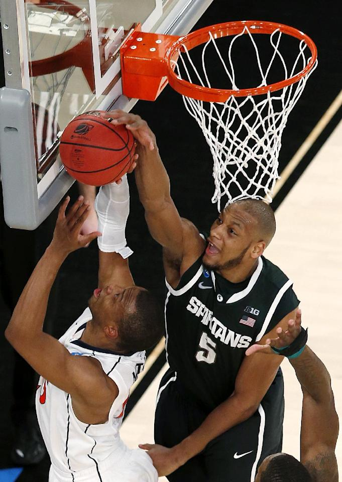 Michigan State forward Adreian Payne, top, blocks a shot by Virginia forward Akil Mitchell during second half of a regional semifinal at the NCAA men's college basketball tournament, early Saturday, March 29, 2014, in New York. (AP Photo/Julio Cortez)